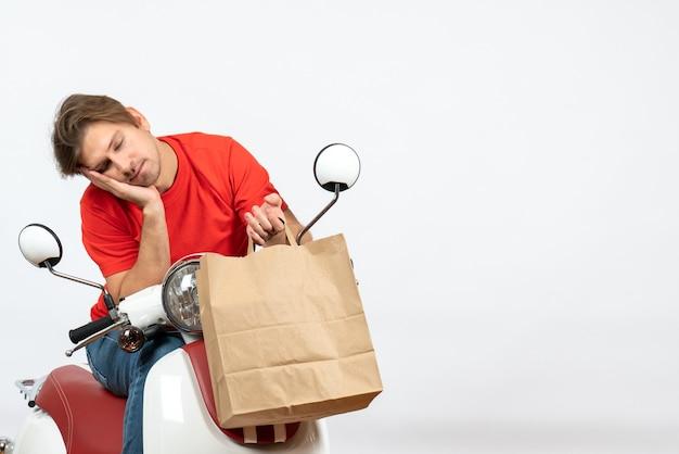 Joven mensajero soñoliento en uniforme rojo sentado en scooter sosteniendo una bolsa de papel en la pared amarilla