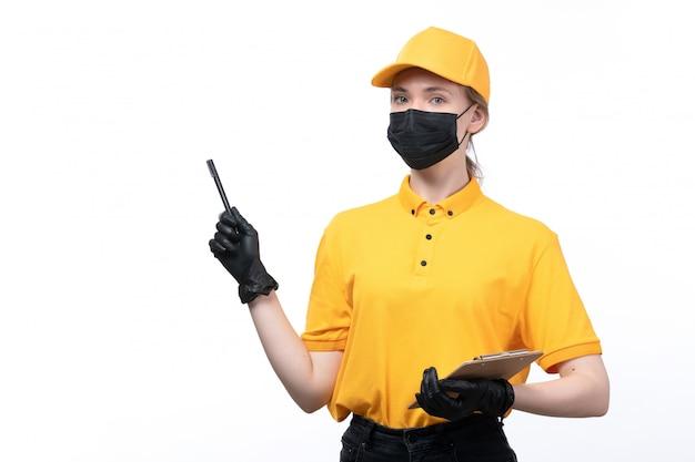 Una joven mensajero de vista frontal en uniforme amarillo guantes negros y máscara negra sosteniendo el bloc de notas tomando un pedido
