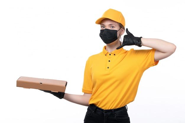 Una joven mensajero de vista frontal en uniforme amarillo guantes negros y máscara negra sosteniendo una caja de pizza vacía