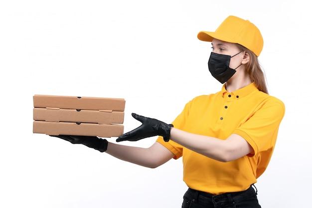 Una joven mensajero de vista frontal en uniforme amarillo guantes negros y máscara negra sosteniendo cajas de pizza