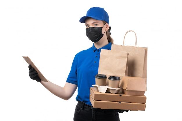 Una joven mensajero de vista frontal en uniforme azul guantes negros y máscara negra con paquetes de entrega de alimentos y bloc de notas