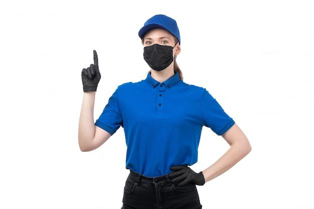 Una joven mensajero de vista frontal en uniforme azul guantes negros y máscara negra posando con sus manos