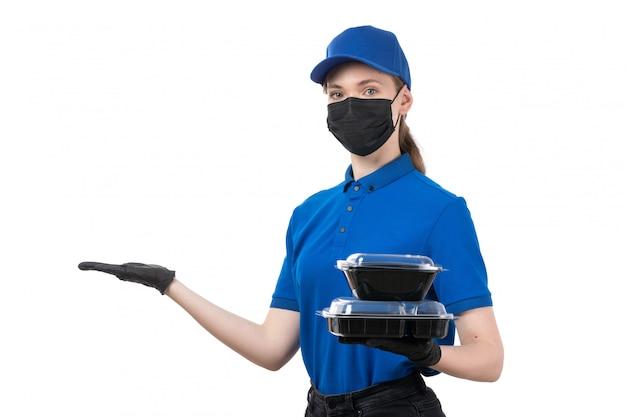 Una joven mensajero de vista frontal en uniforme azul guantes negros y máscara negra sosteniendo cuencos de entrega de alimentos