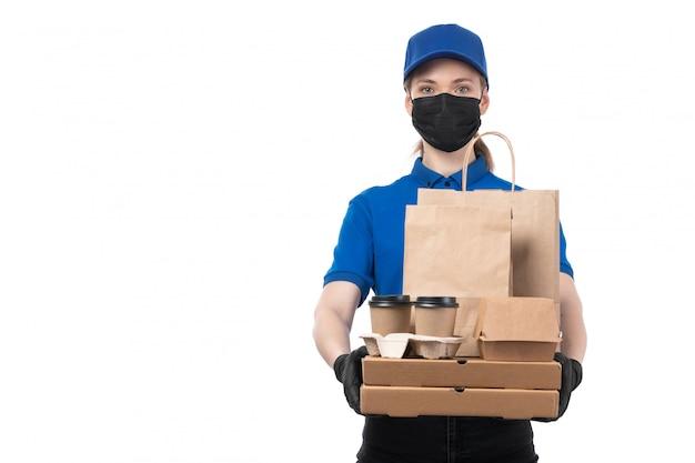 Una joven mensajero de vista frontal en uniforme azul guantes negros y máscara negra sosteniendo paquetes de entrega de alimentos
