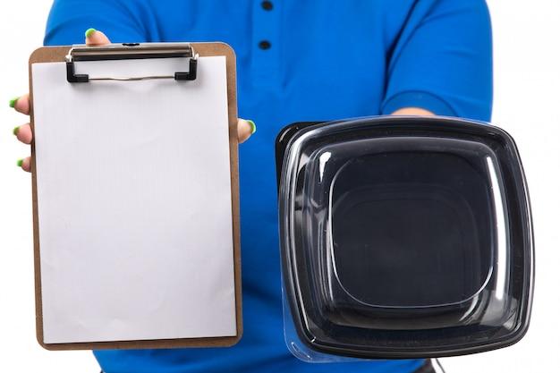 Una joven mensajero de vista frontal en uniforme azul sosteniendo el tazón de entrega de alimentos y el bloc de notas para firmas
