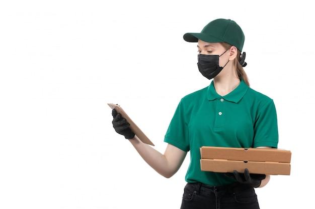 Una joven mensajero de vista frontal en uniforme verde guantes negros y máscara negra con cajas de entrega de alimentos