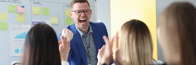 Joven mentor masculino emocional realiza reuniones informativas de negocios a colegas
