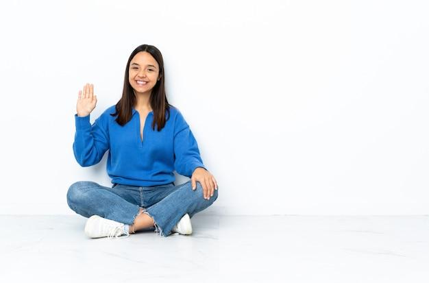 Joven mestiza mujer sentada en el piso aislado en blanco saludando con la mano con expresión feliz