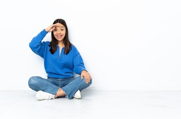 Joven mestiza mujer sentada en el suelo en la pared blanca saludando con la mano con expresión feliz