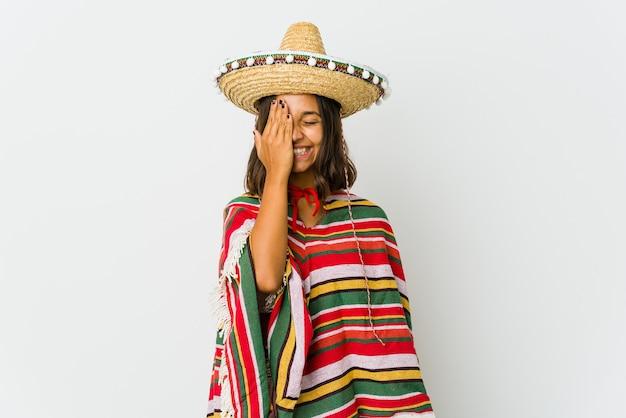 Joven mexicana en blanco divirtiéndose cubriendo la mitad de la cara con la palma.