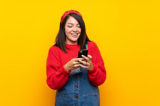 Joven mexicana con monos sobre muro amarillo enviando un mensaje con el móvil