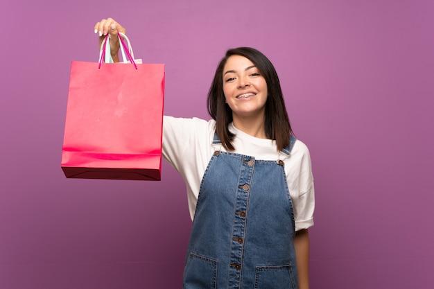 Joven mexicana sobre aislado sosteniendo muchas bolsas de compras
