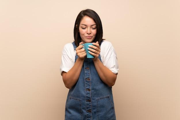 Joven mexicana sobre aislado sosteniendo una taza de café caliente