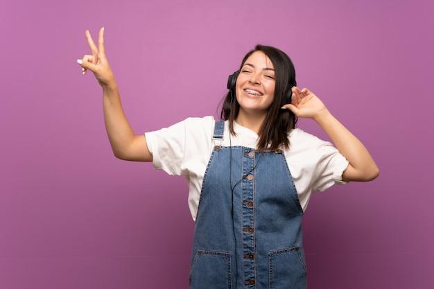 Joven mexicana sobre fondo aislado escuchando música con auriculares