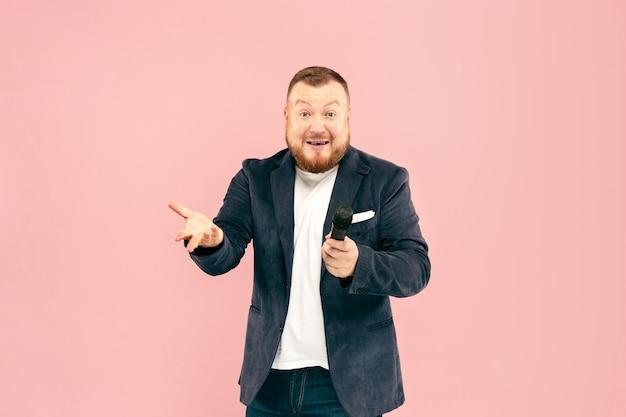 Joven con micrófono en pared rosa
