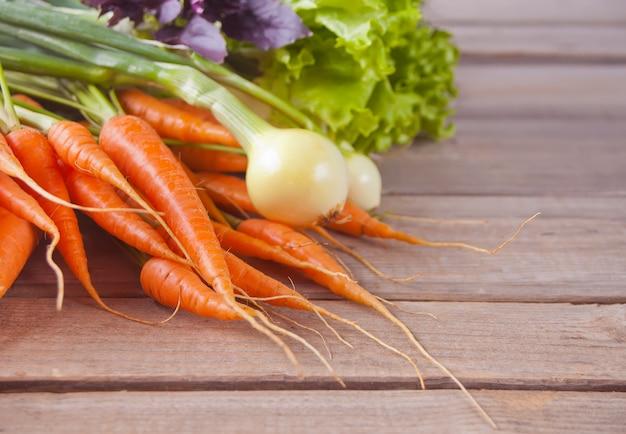 Joven mini zanahoria, cebolla, albahaca en fila sobre fondo de madera