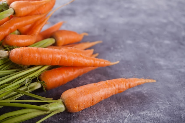 Joven mini zanahoria sobre fondo concreate.