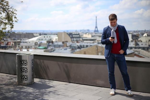 Joven mira en el teléfono inteligente en el techo del edificio alto en parís, cerca de la torre eiffel