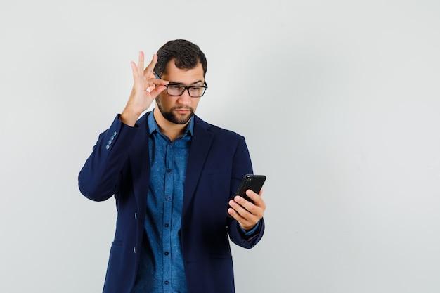 Joven mirando atentamente el teléfono móvil en camisa, vista frontal de la chaqueta.