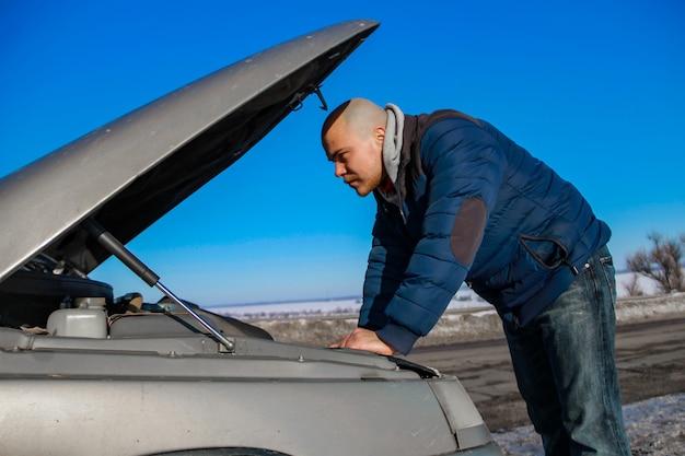 Joven mirando bajo el capó del coche roto en un día frío de invierno