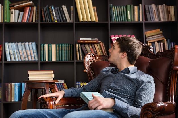 Joven mirando libros en una biblioteca sentado en un cómodo sillón leyendo los títulos de los libros en los estantes