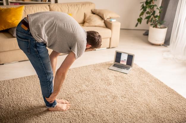 Joven mirando la pantalla del portátil con video de entrenamiento y haciendo ejercicio de yoga en casa, concepto de aislamiento