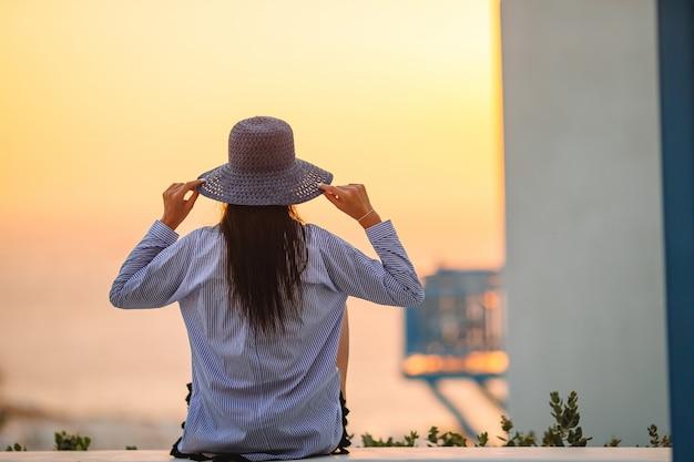 Joven está mirando la puesta de sol sobre un mar en el famoso pueblo de mykonos