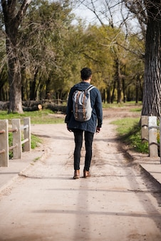 Joven con mochila caminando en el parque