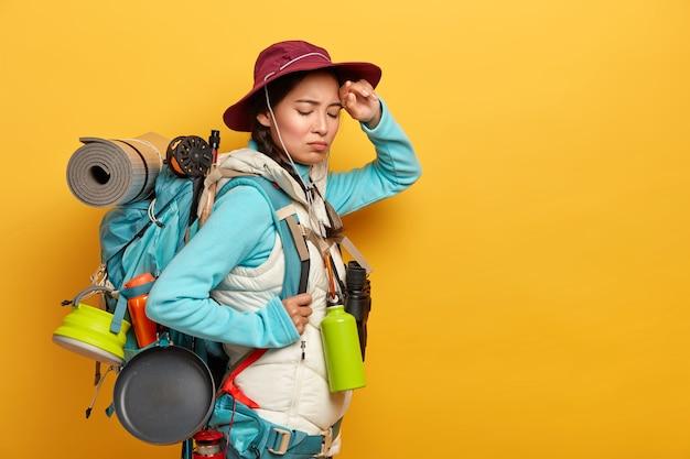 La joven mochilera tiene expresión facial cansada, mantiene la mano en la frente, siente fatiga después de un largo viaje a pie