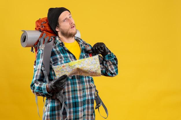 Joven mochilero con guantes de cuero sosteniendo un mapa de viaje apuntando a sí mismo