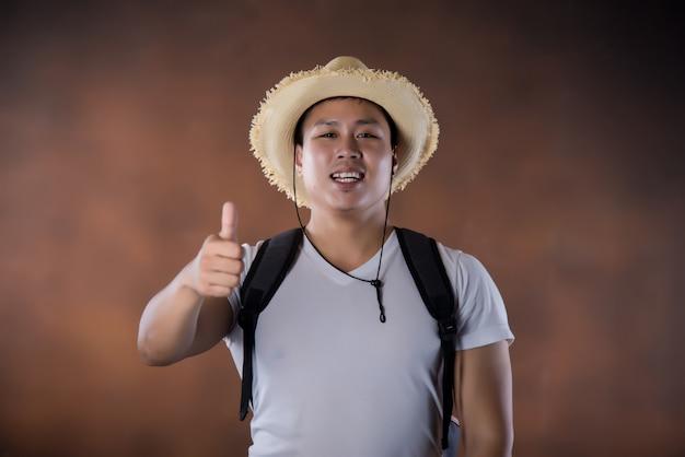 Joven mochilero que viaja asiático con bolsa y sombrero