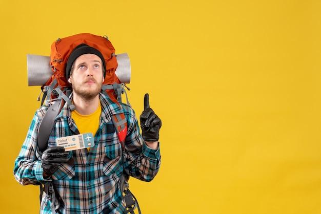 Joven mochilero con sombrero negro sosteniendo billete de viaje apuntando al techo