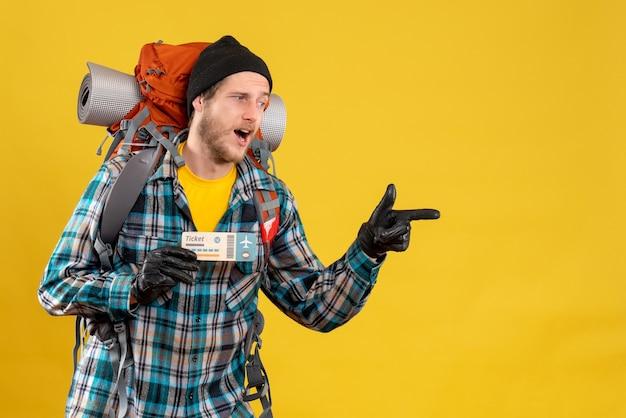 Joven mochilero con sombrero negro sosteniendo billete de viaje apuntando algo