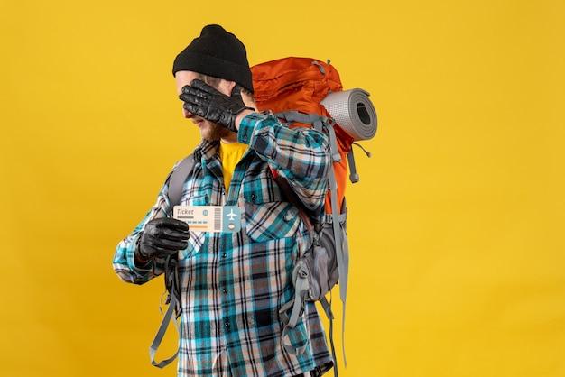 Joven mochilero con sombrero negro sosteniendo boleto de viaje ocultando su rostro