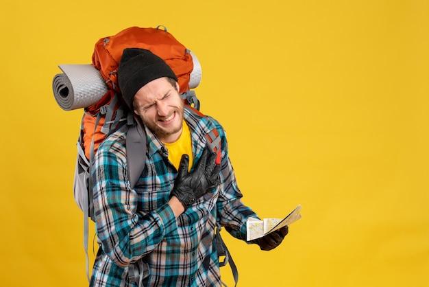 Joven mochilero con sombrero negro sosteniendo un mapa de viaje y su corazón con dolor