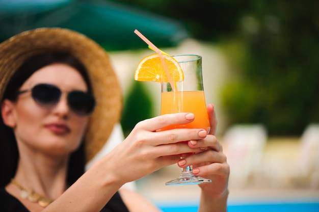 Joven modelo bronceado en elegante traje de verano disfrutando de la fiesta en la piscina, sosteniendo un sabroso cóctel de alcohol.