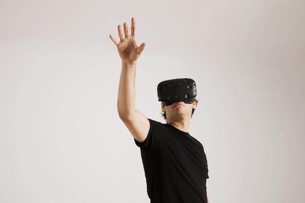 Joven modelo europeo en camiseta de algodón básica en blanco y gafas de realidad virtual tocando algo aislado en blanco