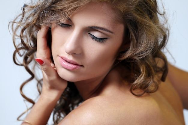 Una joven modelo femenina cierra los ojos