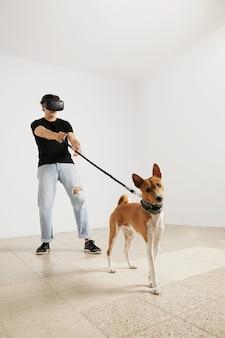Una joven modelo en gafas de realidad virtual, jeans y camiseta negra en blanco sosteniendo un perro basenji con correa