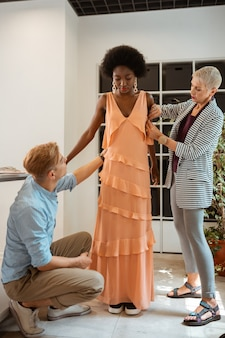 Joven modelo luciendo un nuevo vestido naranja de pie junto a dos diseñadores de moda en un estudio.