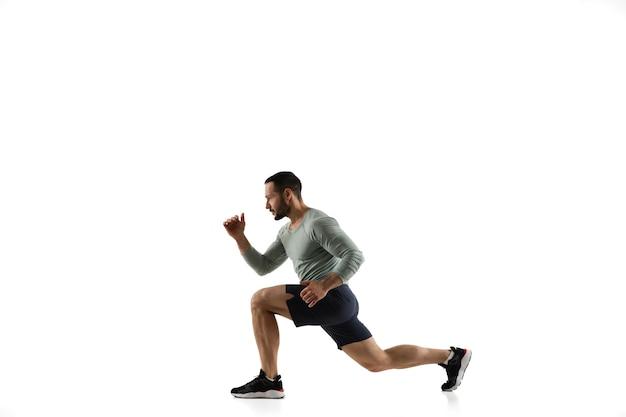 Joven modelo masculino caucásico en acción, movimiento en blanco