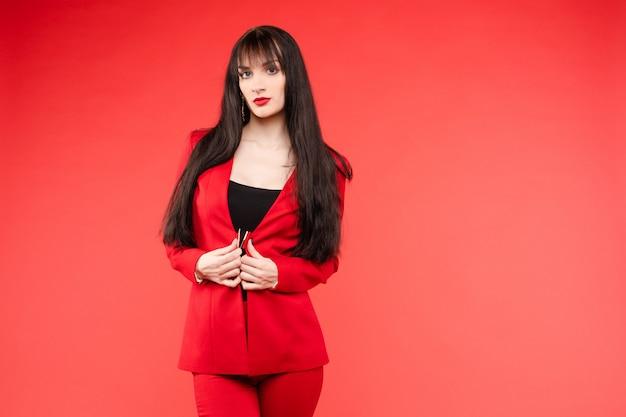 Joven modelo morena en traje rojo posando cerca de globos
