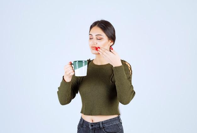 Una joven modelo de mujer bonita disfrutando de una taza de té caliente
