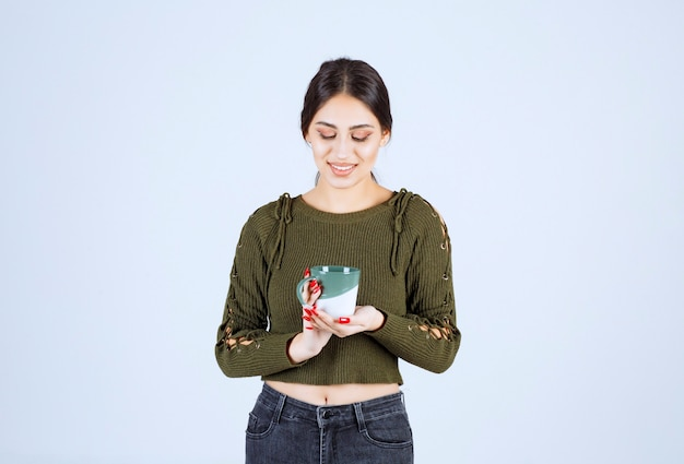 Una joven modelo de mujer bonita en suéter verde mirando una taza