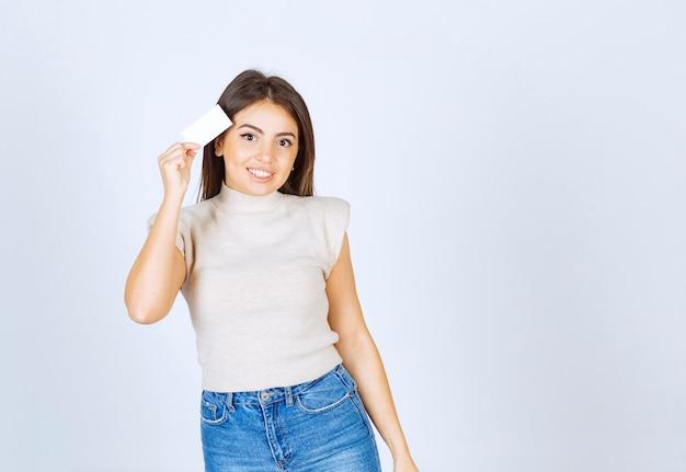 Un joven modelo de mujer sonriente sosteniendo una tarjeta y posando sobre una pared blanca.