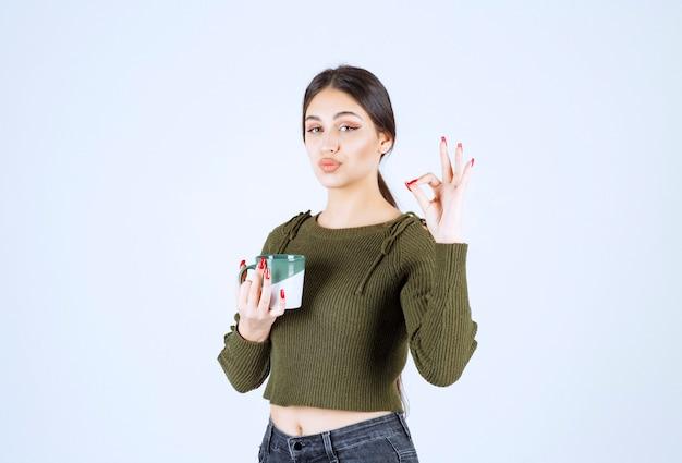 Un joven modelo de mujer sonriente sosteniendo una taza y mostrando un gesto bien.