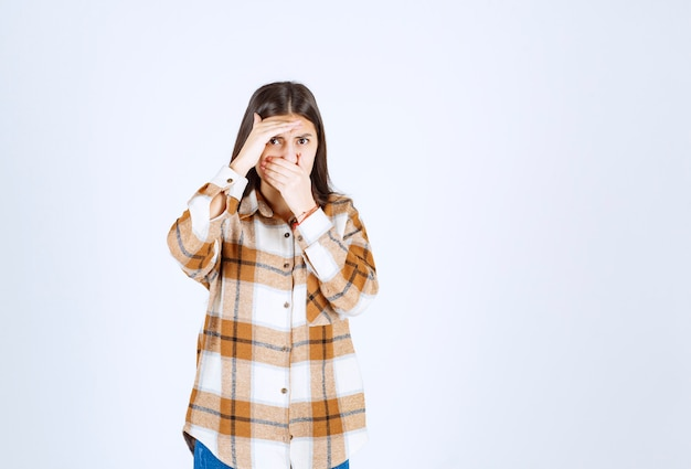 Una joven modelo de pie y tapándose la nariz.