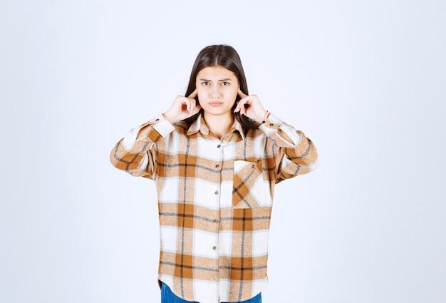 Una joven modelo de pie y tapándose las orejas.