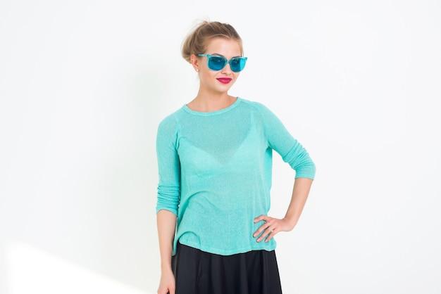 Joven modelo rubia posando en el estudio, realizando un nuevo look de glamour de moda, con gafas de sol, poniendo su brazo en la cadera