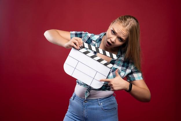 Joven modelo rubia sosteniendo una placa de chapaleta de filmación de películas en blanco.